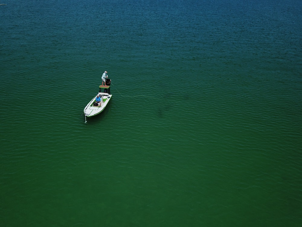man in white and red shirt riding white and blue boat on green sea during daytime