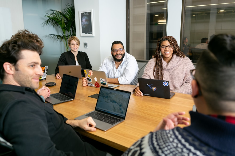 four people all on laptops, two men and two women, listen to person talking in a board meeting