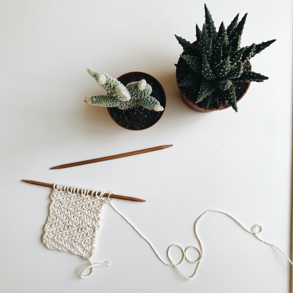 silver and black pine cone and white knit textile