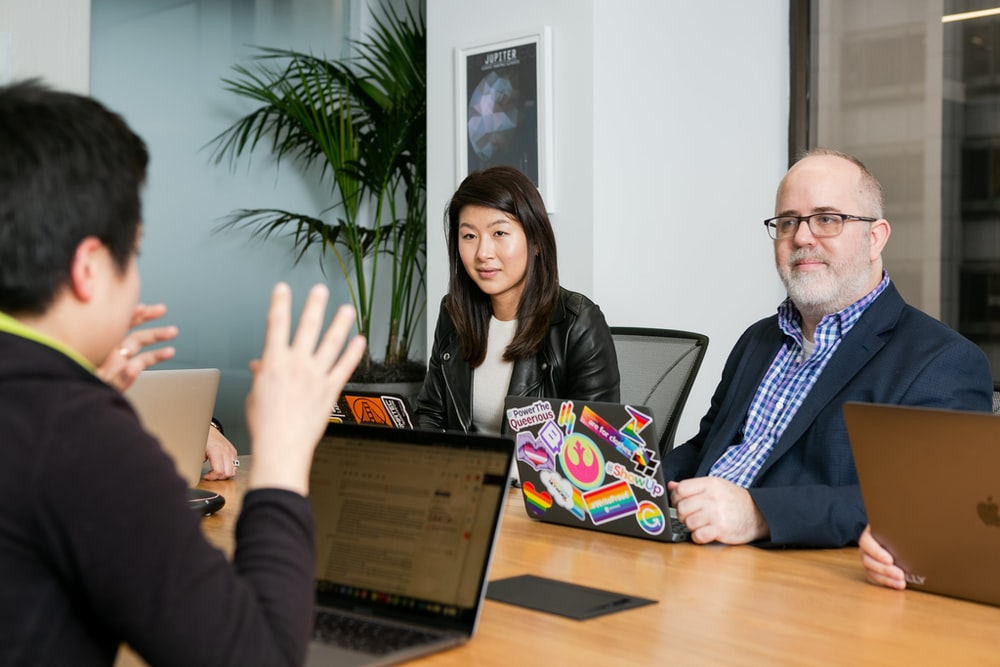 boardroom meeting where woman in black leather jacket and man in blue checkered shirt, suit jacket and glasses, pay attention to person talking with their hands wearing black long sleeve shirt