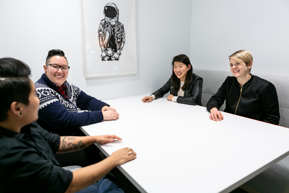 group of four people smiling sitting around white boardroom table