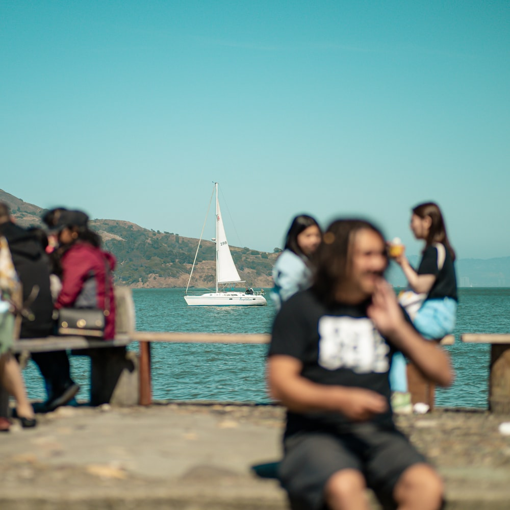 people sitting on brown wooden dock during daytime