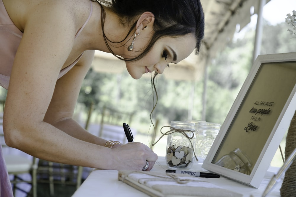 woman in white tank top writing on white paper
