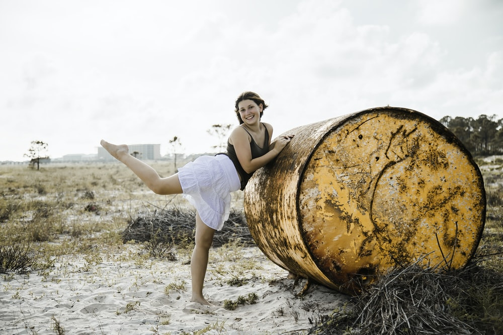 woman in white t-shirt and white shorts sitting on brown wooden barrel