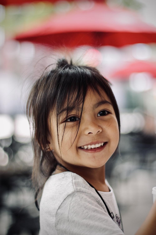 girl in white collared shirt smiling