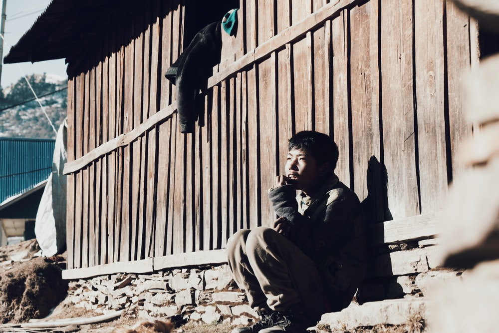 man in black jacket sitting on brown concrete stairs