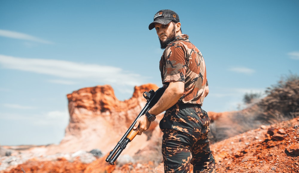 man in brown and black camouflage shirt holding rifle