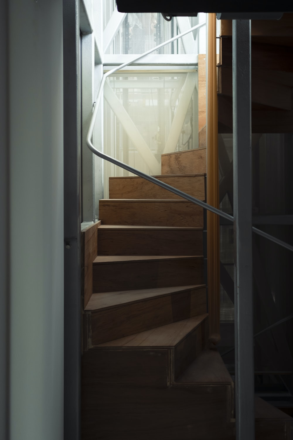 brown wooden staircase near glass window