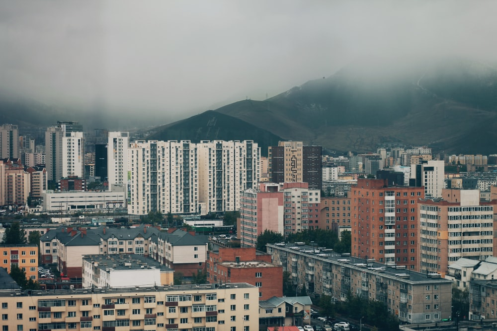 high rise buildings near mountain during daytime