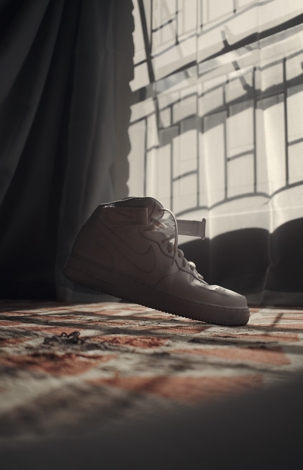 black leather lace up boots on red and brown area rug