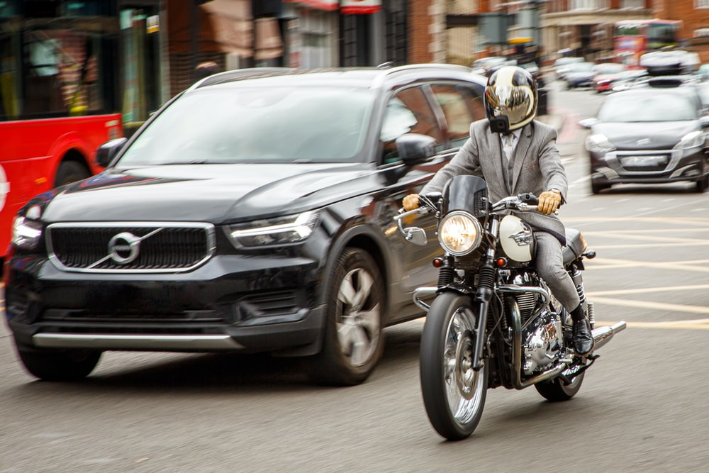 man in gray jacket riding motorcycle