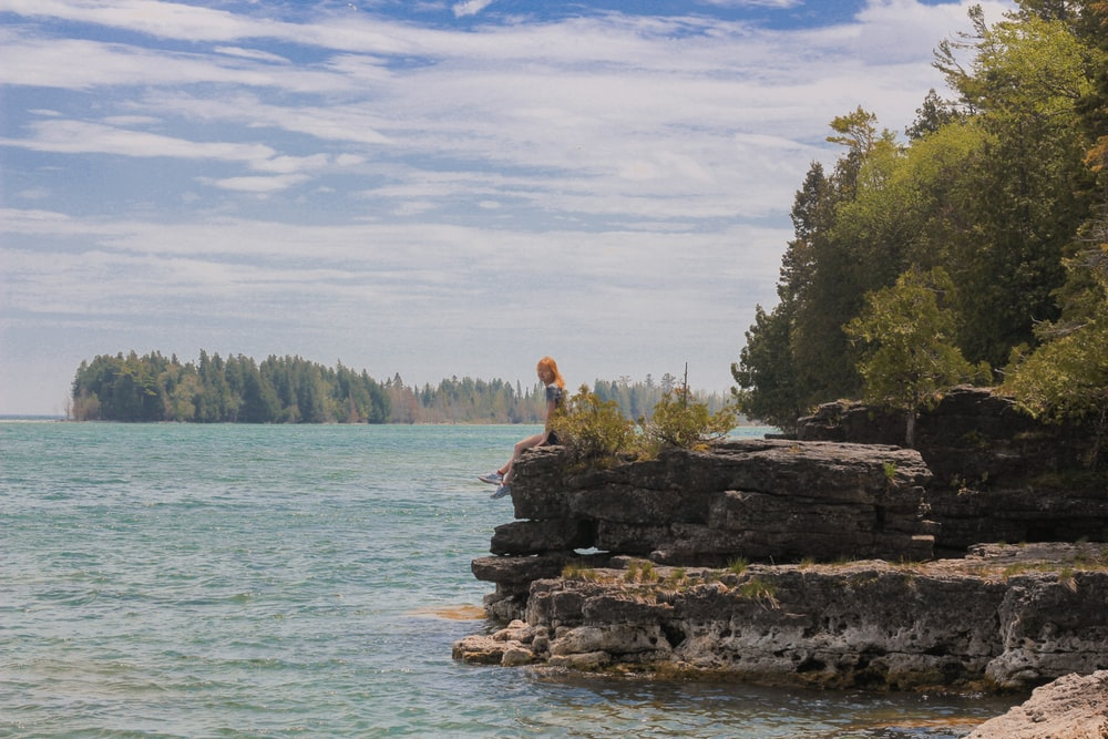 person sitting on rock formation near body of water during daytime