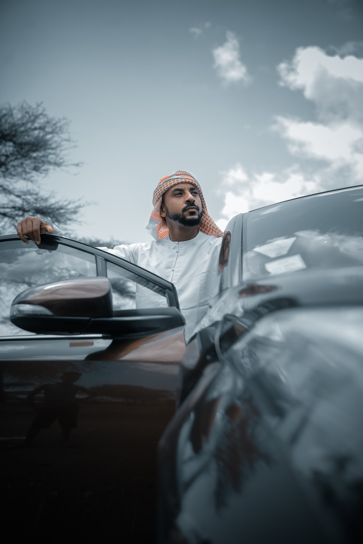 man in white thobe standing beside car during daytime