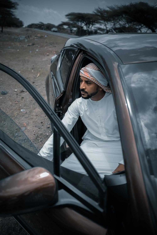woman in white hijab sitting on car