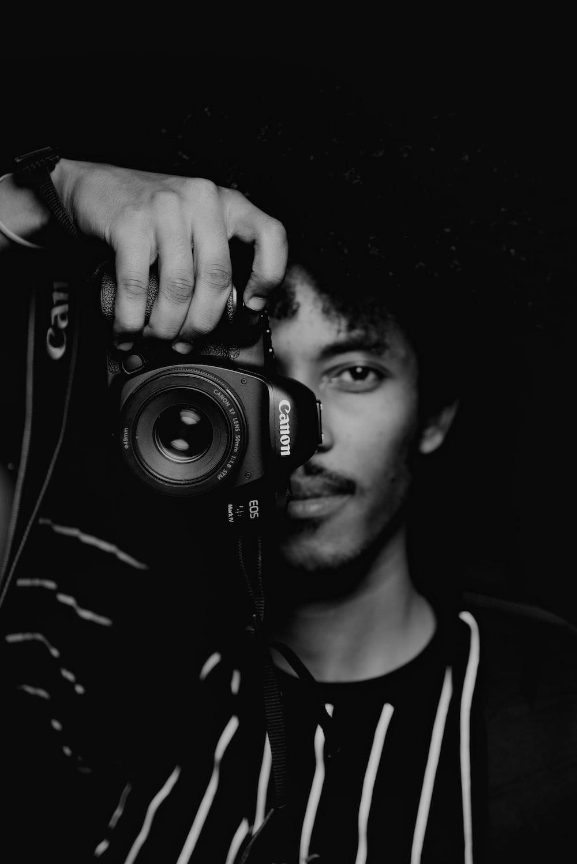 man in black and white crew neck shirt holding black nikon dslr camera