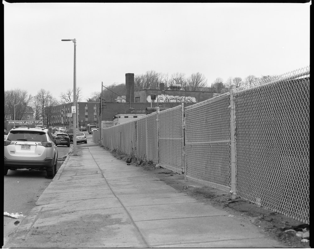 grayscale photo of a road with metal fence