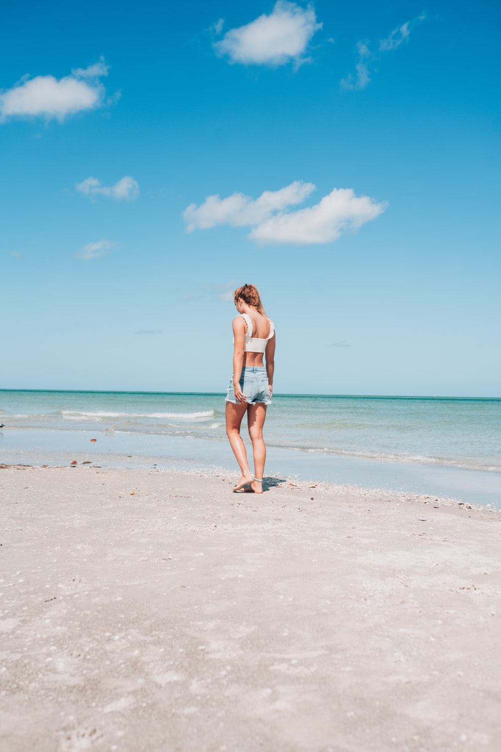woman in blue bikini standing on beach during daytime