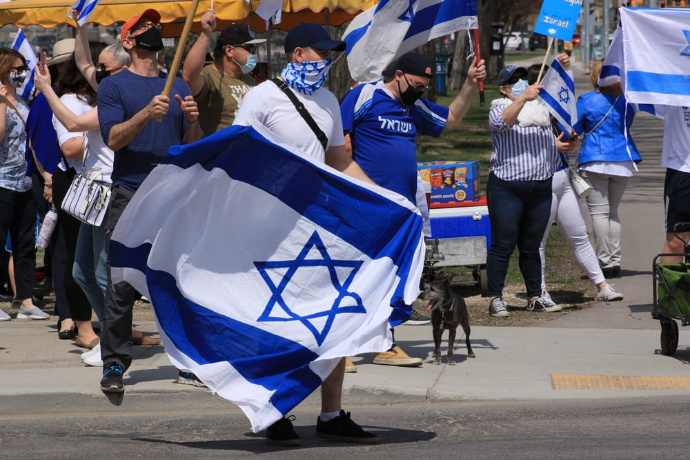 people in blue and white flags walking on street during daytime