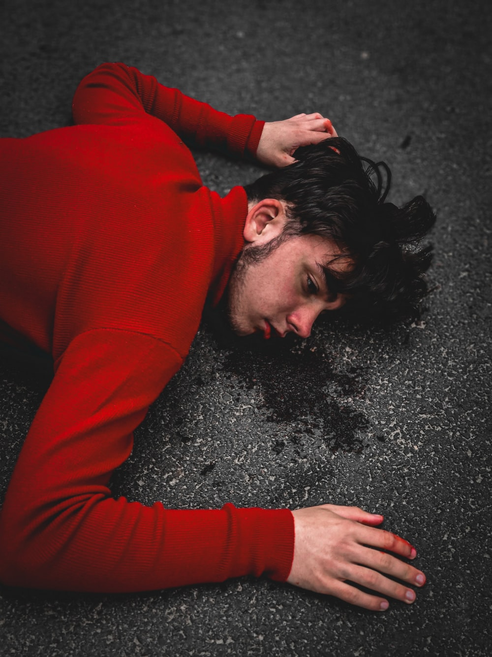woman in red long sleeve shirt lying on black sand