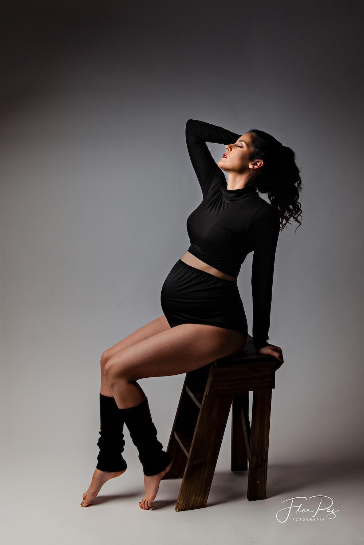 woman in black long sleeve dress sitting on brown wooden seat