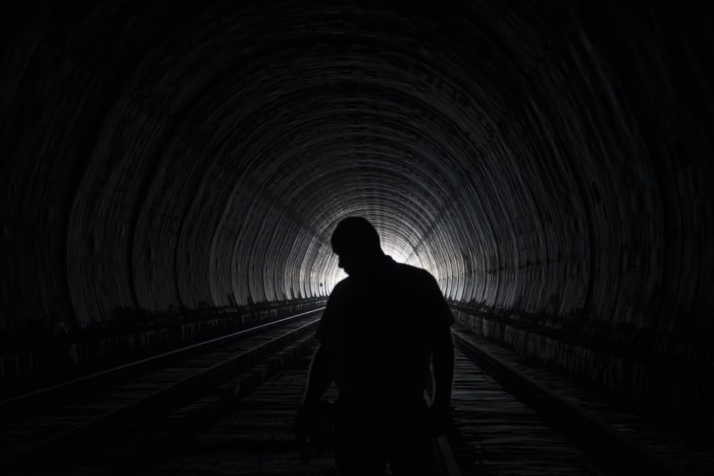 silhouette of person walking on tunnel during daytime