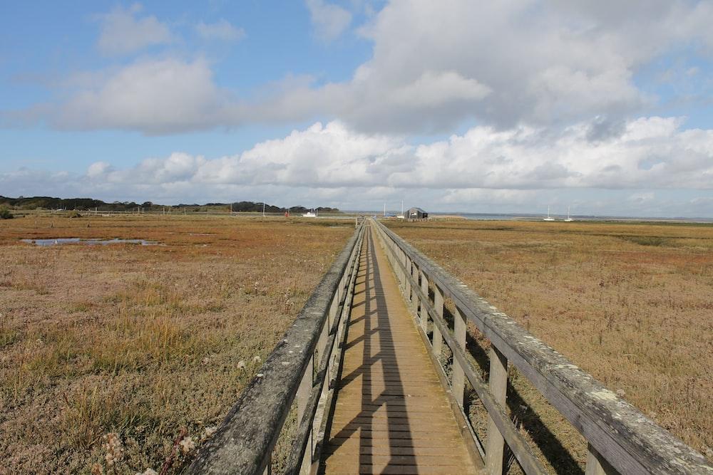 brown wooden bridge on brown grass field under white clouds during daytime