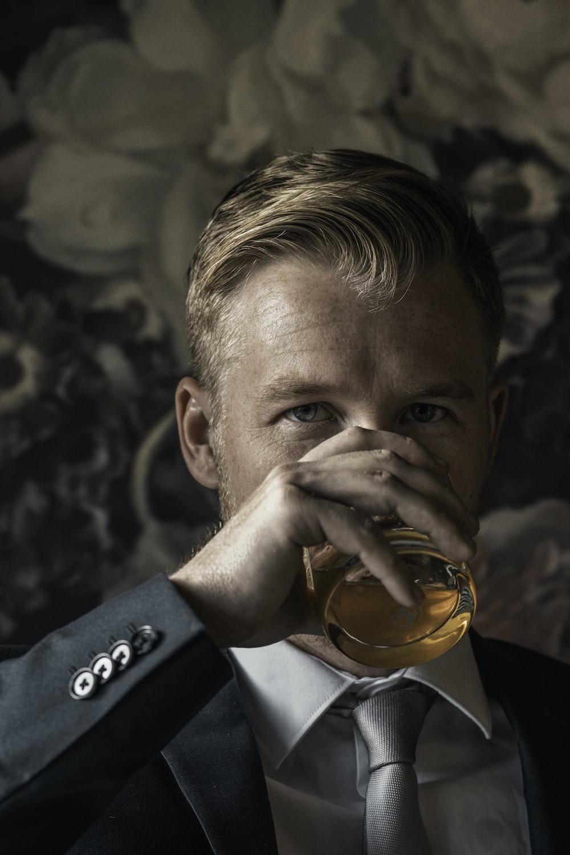 man in black suit drinking