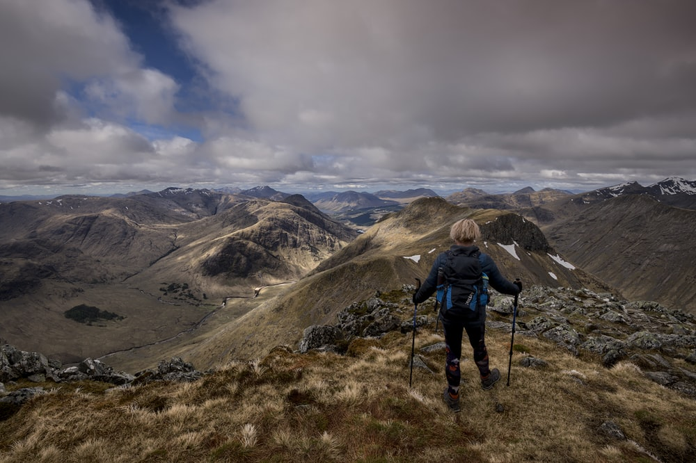 person in blue jacket and black pants with black hiking bag on mountain under white clouds
