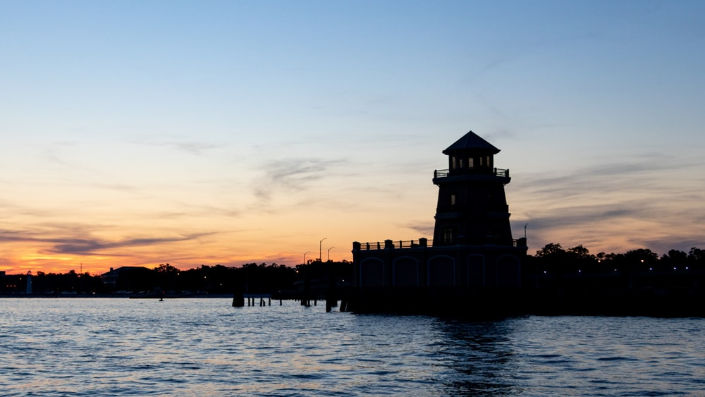 silhouette of building near body of water during sunset