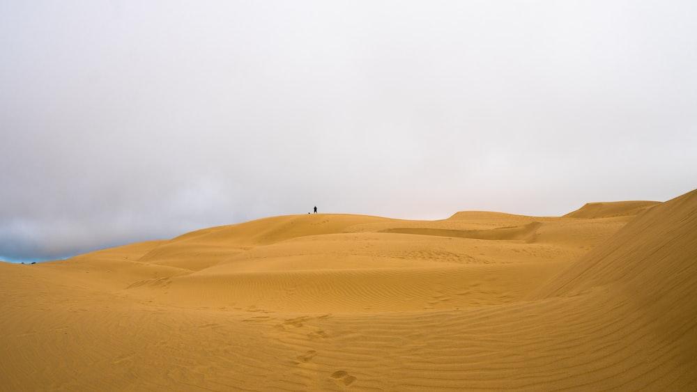 person walking on desert during daytime
