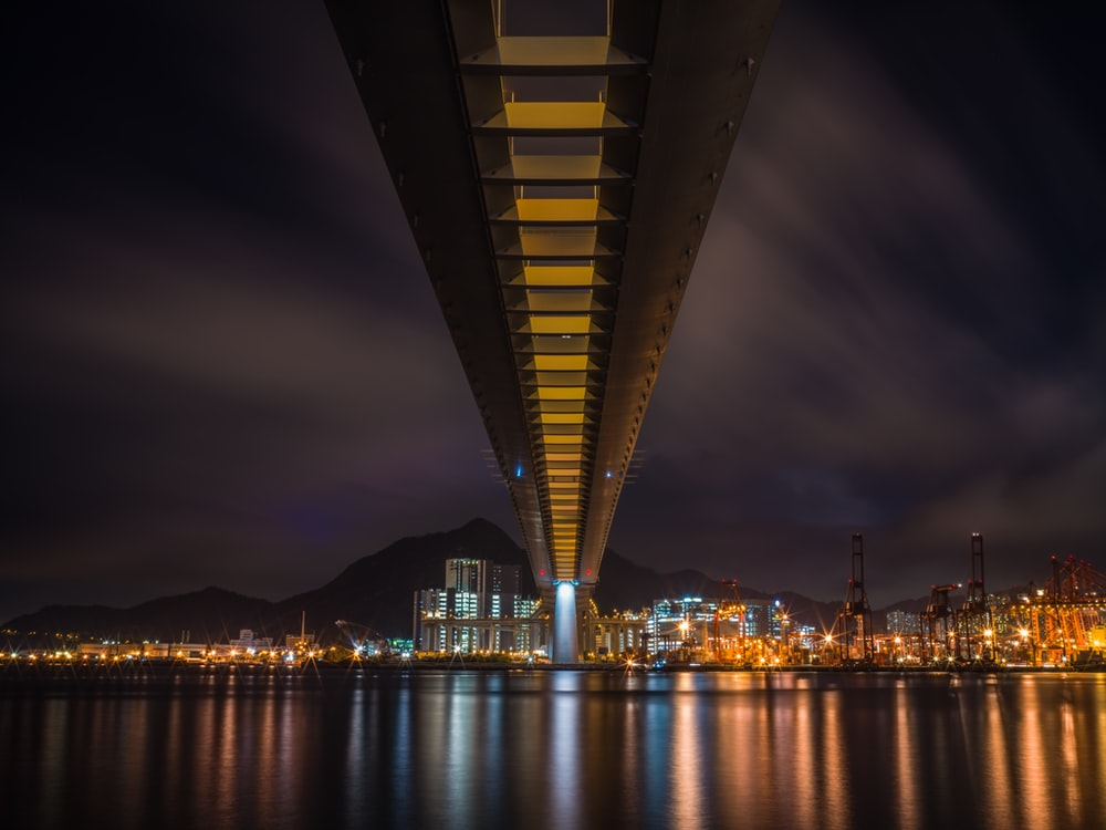 lighted bridge over body of water during night time