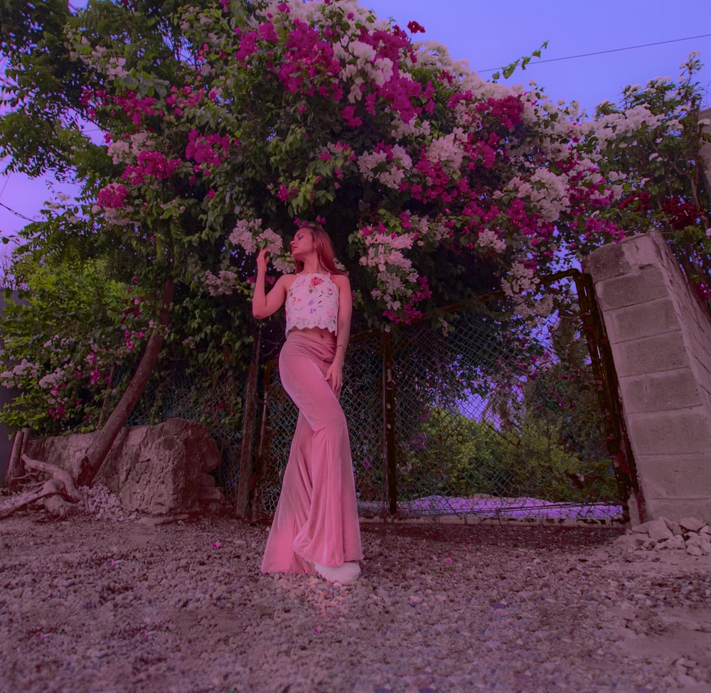 woman in pink dress standing near brown concrete wall during daytime