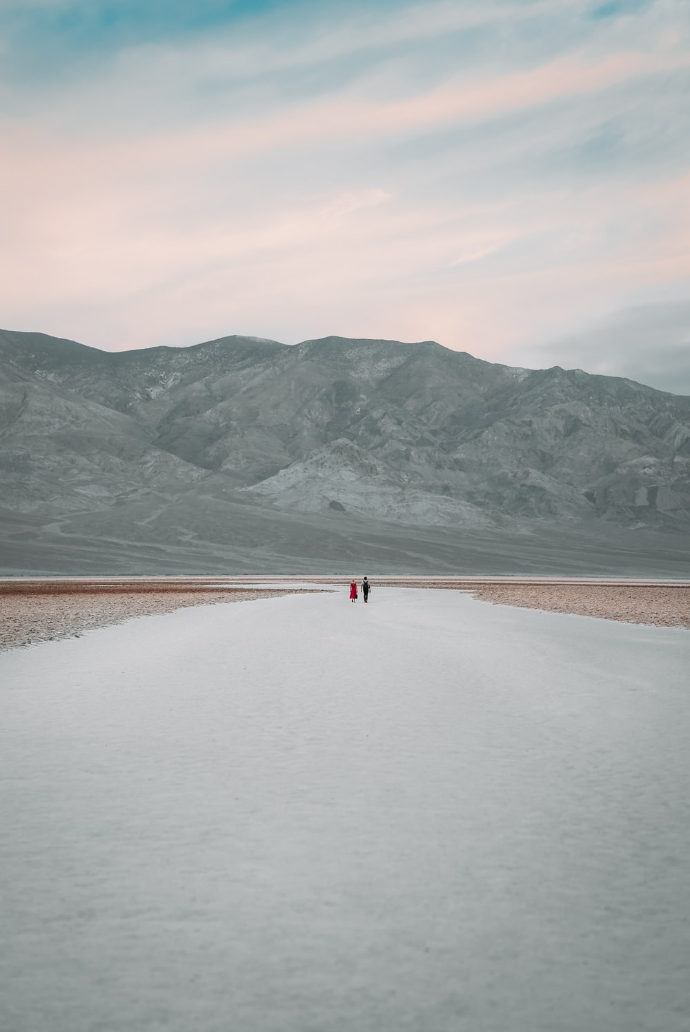 person walking on brown sand near lake and mountains during daytime