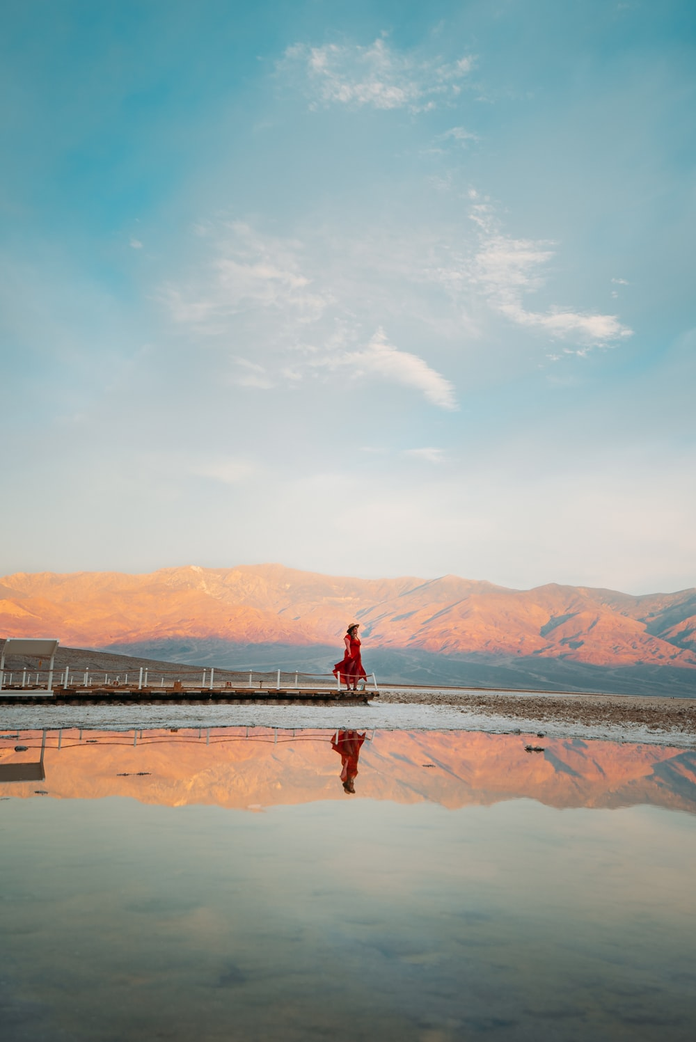 person in red jacket standing on brown sand near body of water during daytime