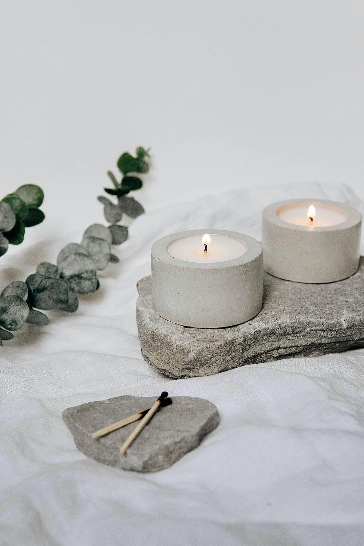 white pillar candle on gray rock
