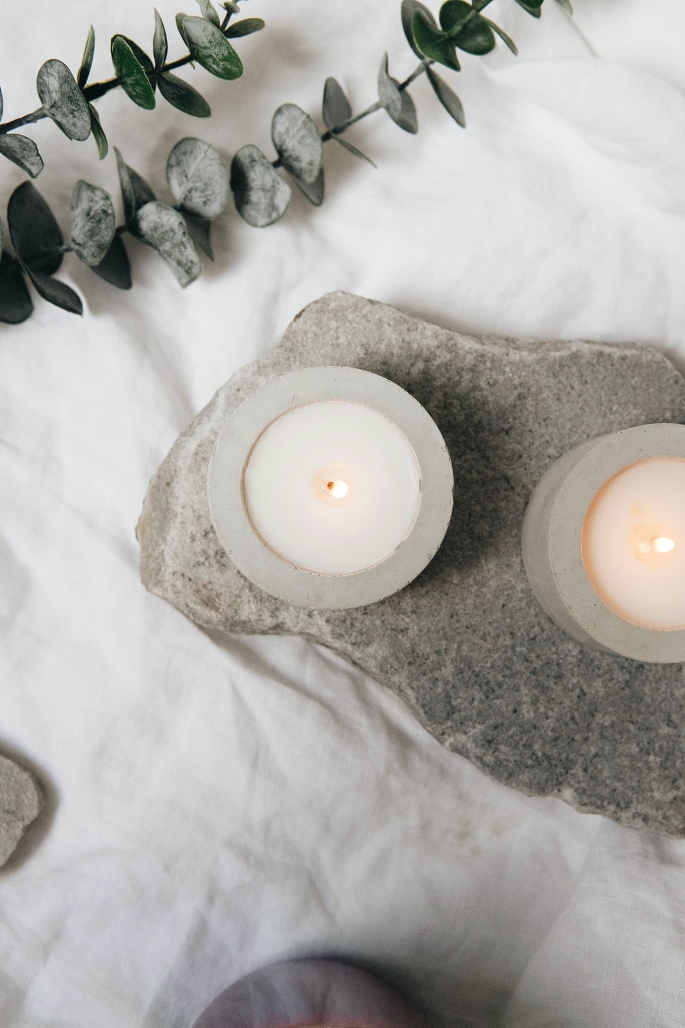 white candle on white ceramic saucer