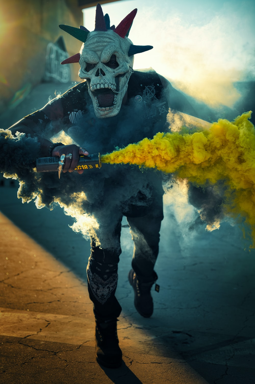 man in black and white mask holding black and yellow power tool