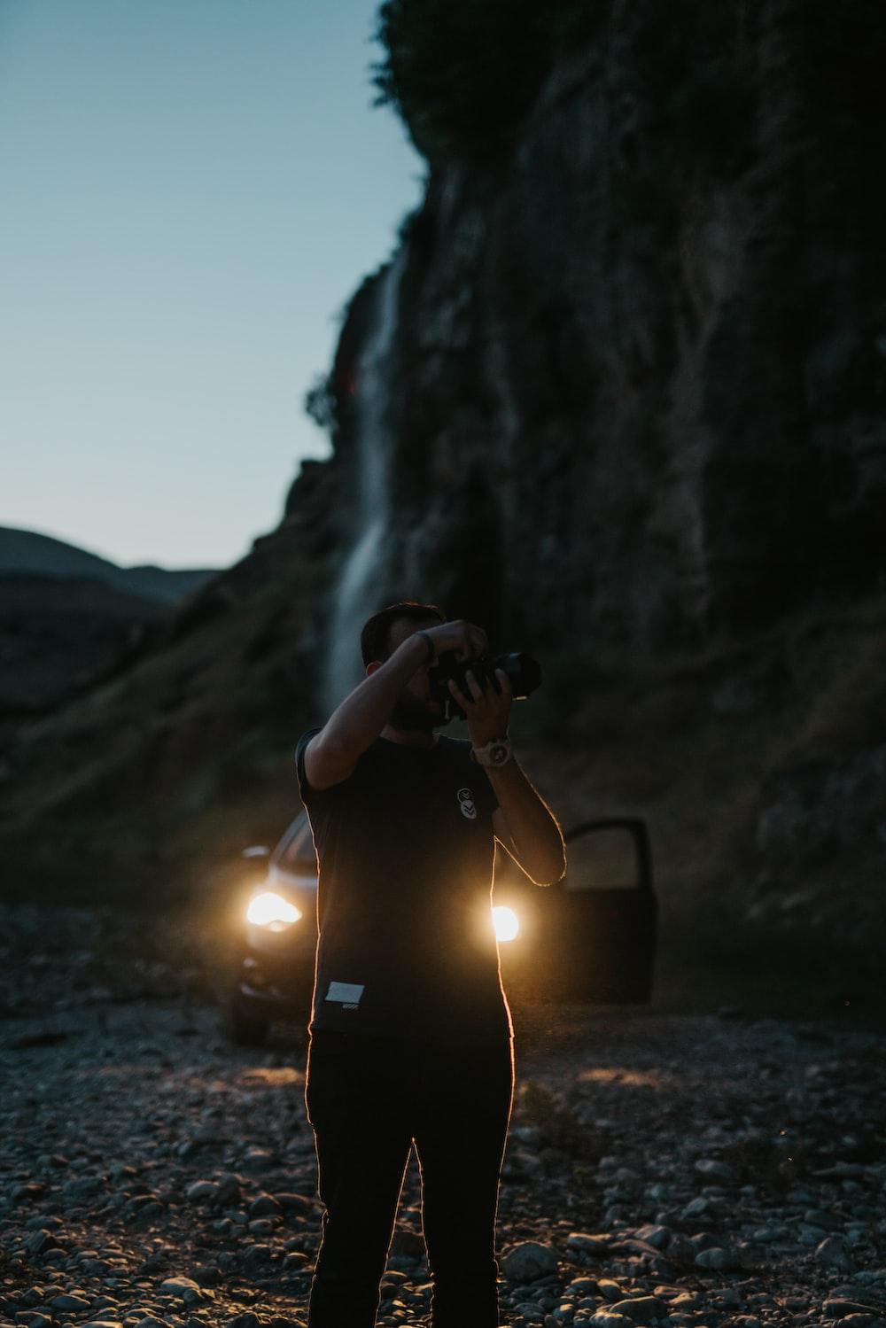 person in black jacket sitting on rock near waterfalls during daytime