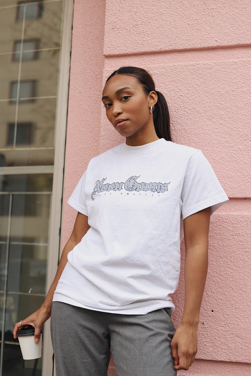 woman in white crew neck t-shirt standing beside brown concrete wall