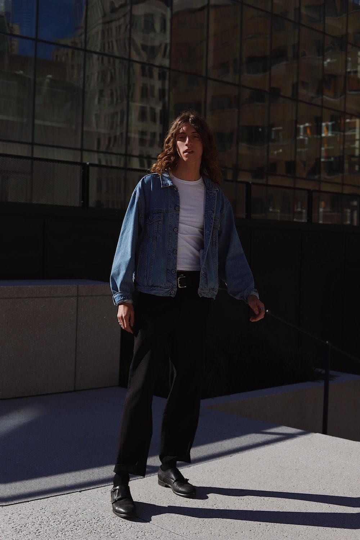 woman in blue denim jacket and black pants standing on blue floor