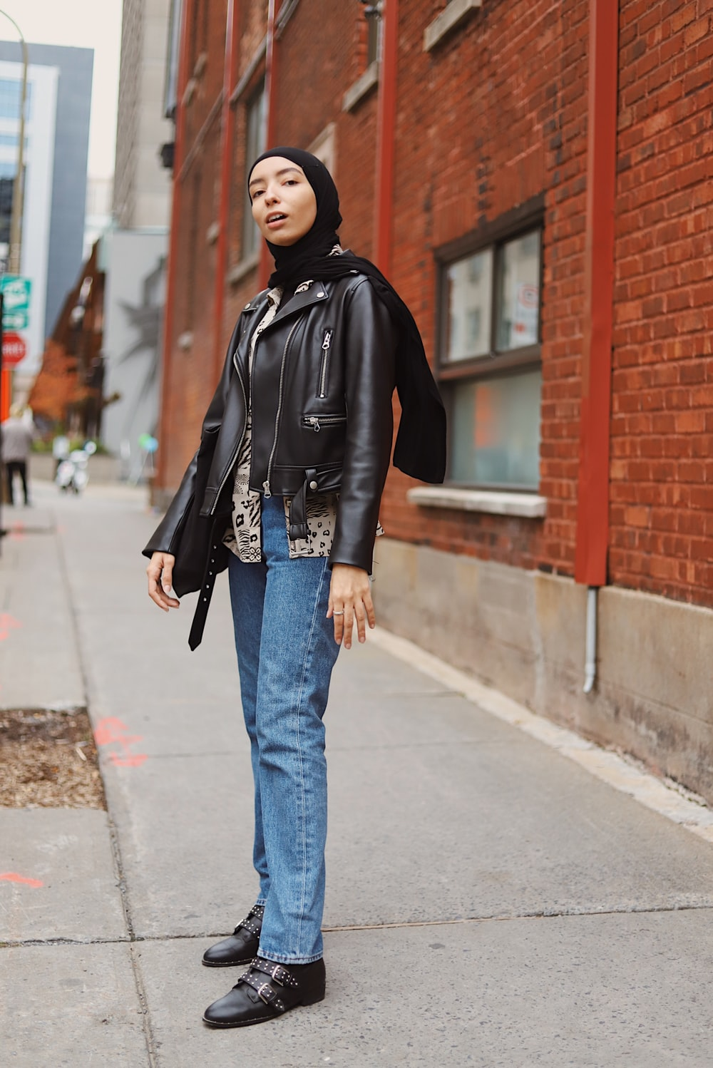 woman in black leather jacket and blue denim jeans standing on sidewalk during daytime