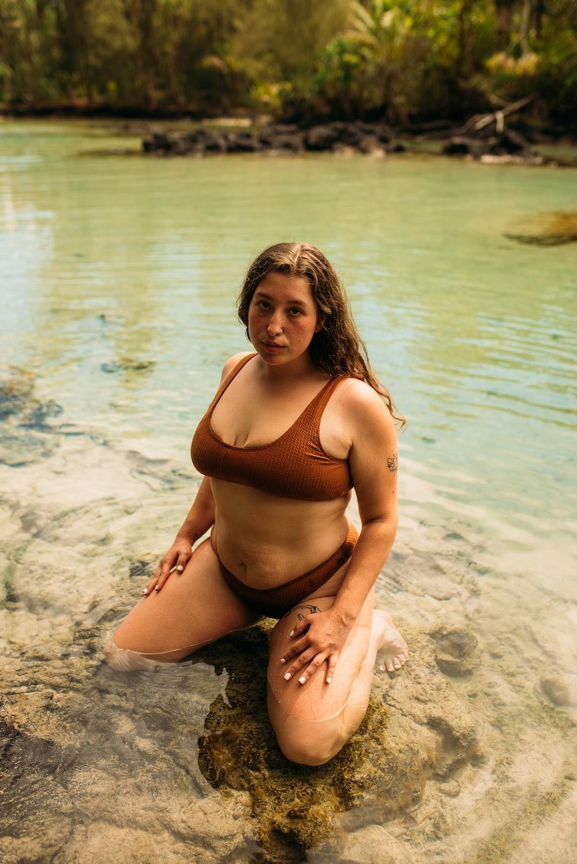 woman in black bikini sitting on beach during daytime