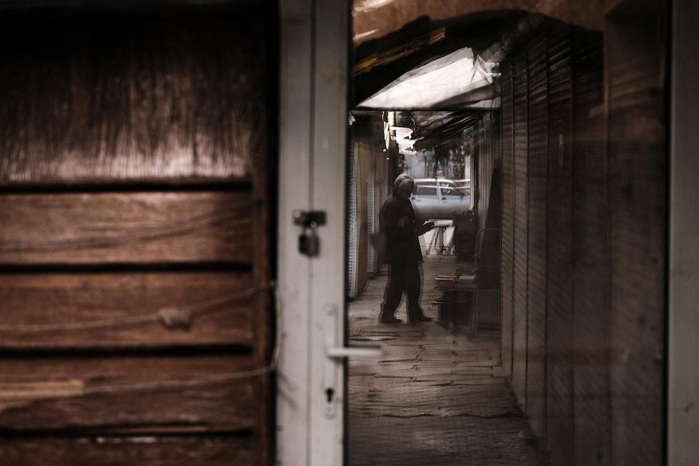 man in black jacket and pants standing in front of door