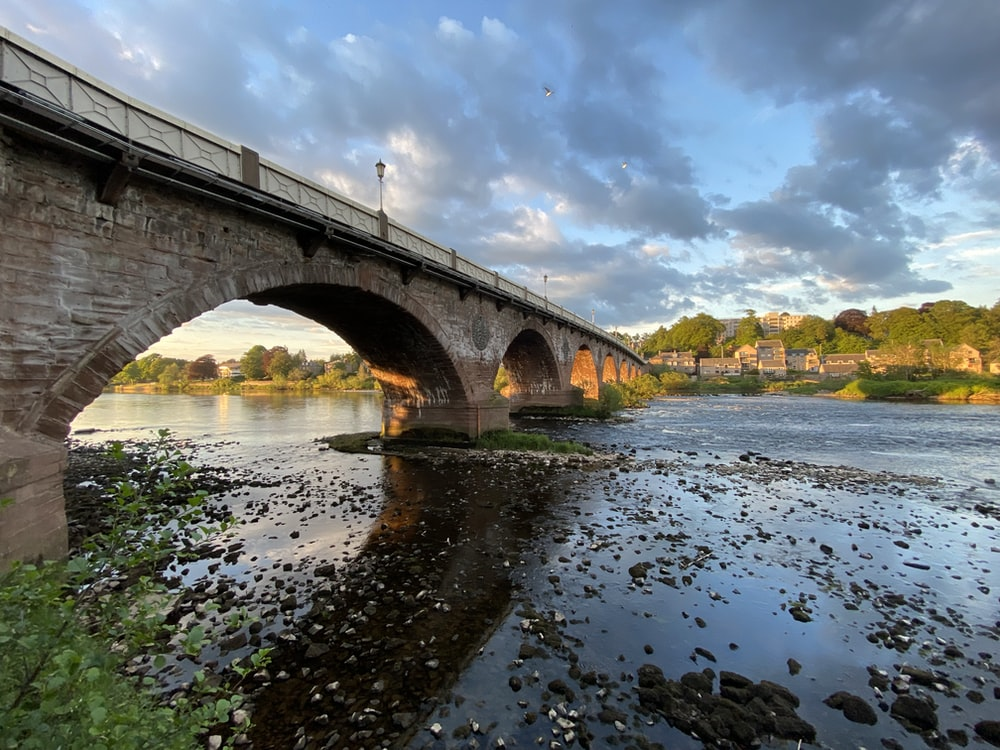 brown concrete bridge over river under blue sky and white clouds during daytime