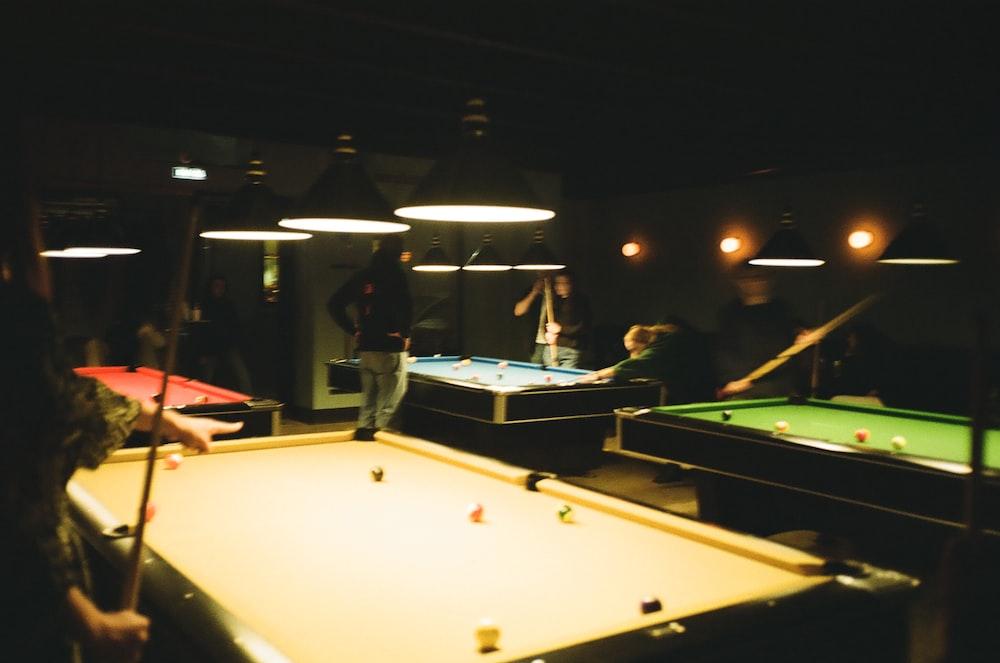 man in black jacket standing near billiard table