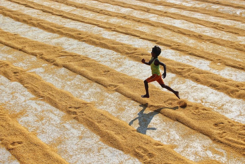 man in black shirt walking on brown sand during daytime