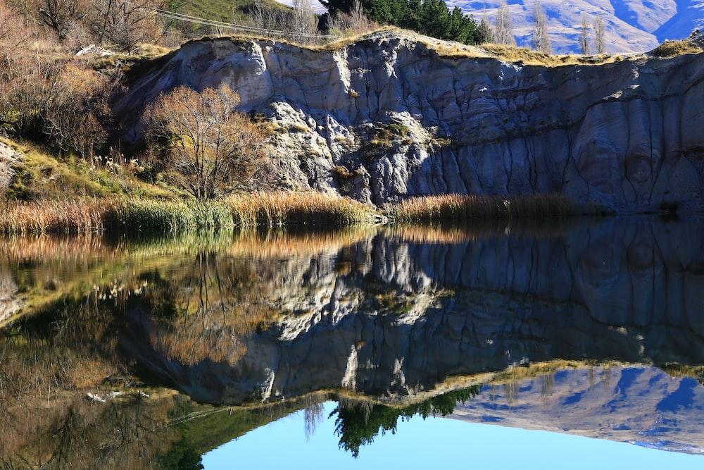 gray rocky mountain beside lake during daytime