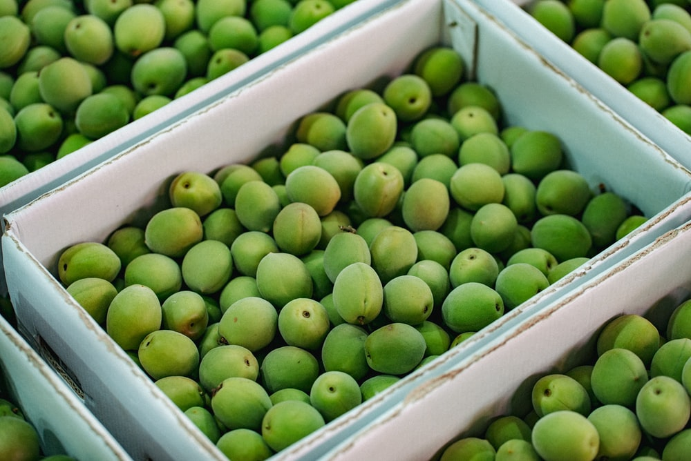 green fruits in white plastic crate