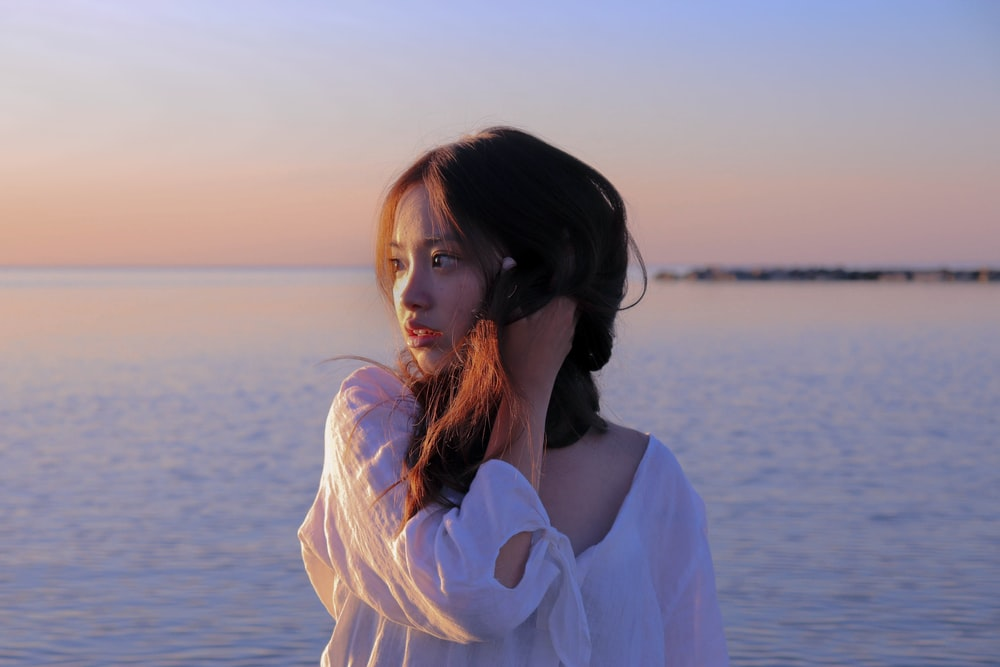 woman in white long sleeve shirt standing near body of water during daytime