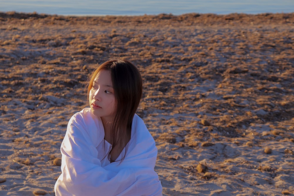 woman in white hoodie standing on brown sand during daytime